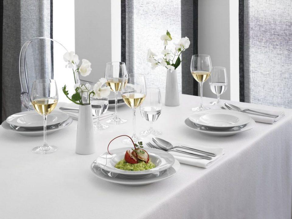 Weingläser und weißes Porzellan auf weiß gedecktem Tisch