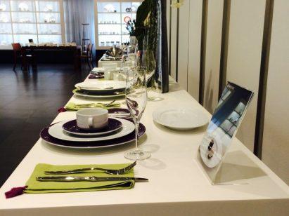 Besteck und Geschirr in Lila und Grüntönen auf Tisch mit weißer Tischdecke präsentiert
